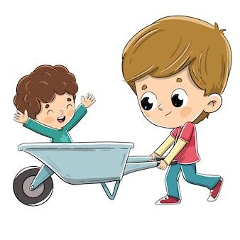 Het spelen van de jongen met een kruiwagen die zijn broer loopt