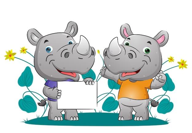 Het stel slimme neushoorns die iets uitleggen terwijl ze de afbeelding op het lege bord vasthouden