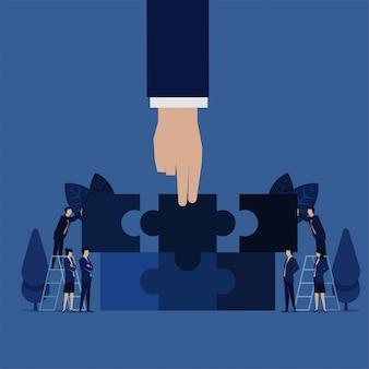Het stuk puzzelstukjes uit de zakelijke hand wordt verenigd om de puzzelmetafoor van samenwerking en teamwerk te matchen.