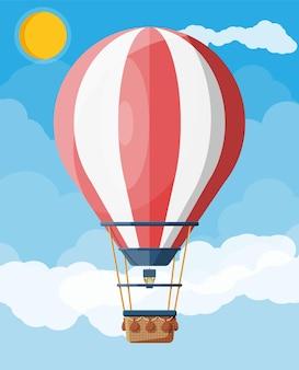 Hete luchtballon in de lucht met wolken en zon. vintage luchtvervoer. aerostaat met mand. platte vectorillustratie