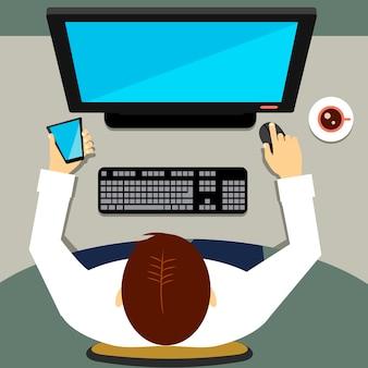 Hoge hoek van een man die op kantoor zit en op een desktopcomputer werkt