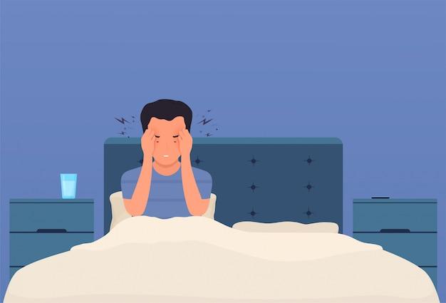 Hoofdpijn. een man in bed heeft hoofdpijn, migraine, druk op het hoofd. vermoeide persoon met hevige pijn in de slapen drukt handen tegen het hoofd.