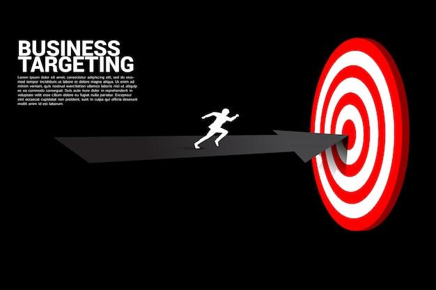 Hoogste meningssilhouet die van zakenman op pijl aan centrum van dartboard lopen.