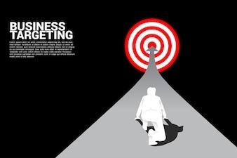 Hoogste meningssilhouet van zakenman klaar om op pijl aan centrum van dartboard te lopen.