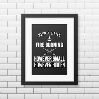 Houd een beetje vuur brandend, hoe klein maar verborgen ook - citeer typografische achtergrond in het realistische vierkante zwarte frame op de bakstenen muurachtergrond.