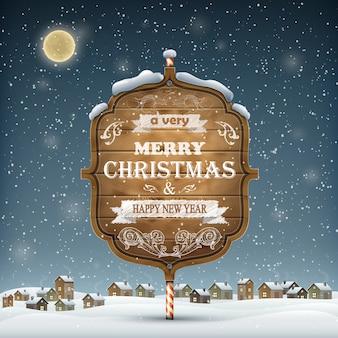 Houten kerst uithangbord in de sneeuw.