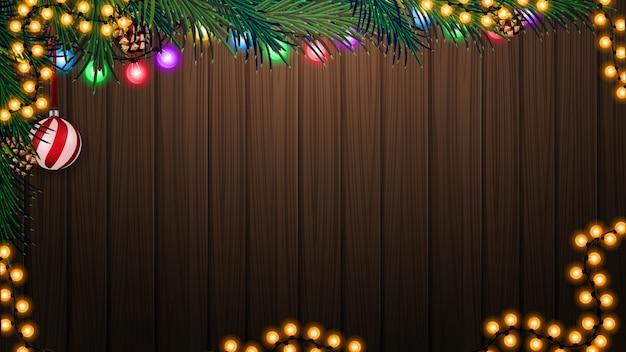 Houten muur met kerstboomtak en kerstmisdecor op houten achtergrond