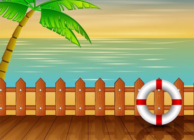 Houten pier met uitzicht op de zee met palmboom en reddingsboei