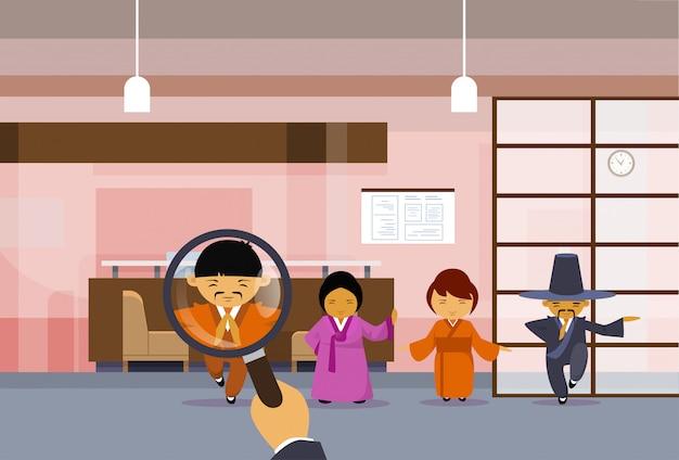 Hr hand hold vergrootglas kiezen zakenman over groep chinese mensen uit het bedrijfsleven