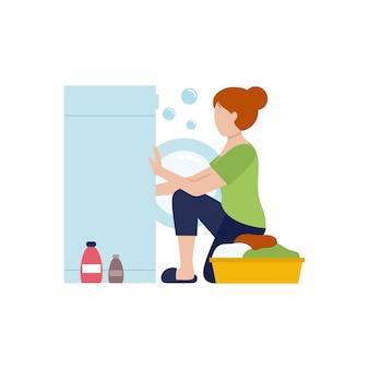 Huisvrouw meisje zet kleren in de wasmachine. kleding wassen met poeder. vector plat karakter. schoonmaak van het appartement tijdens de quarantaine.