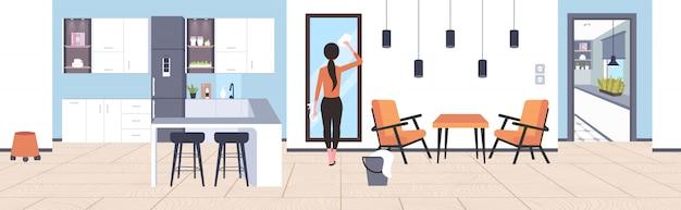 Huisvrouw met stof doek spray fles achteraanzicht vrouw schoner afvegen glas spiegel schoonmaak service concept modern studio appartement woonkamer keuken interieur volledige lengte horizontaal
