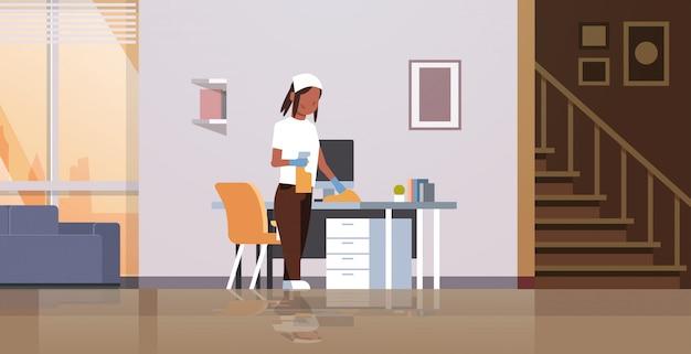 Huisvrouw schoonmaken computertafel met stofdoek vrouw afvegen werkplek bureau huishoudelijk werk concept moderne woonkamer interieur vrouwelijke stripfiguur volledige lengte horizontaal