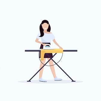Huisvrouw strijken kleding jonge vrouw met ijzer lachend meisje huishoudelijk werk concept doen vrouwelijke cartoon karakter volle lengte platte witte achtergrond