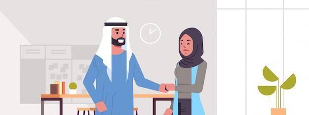 Ic ondernemers man vrouw handshaking arab zakenpartners paar handbewegingen tijdens vergadering overeenkomst partnerschap concept modern co-working centrum kantoor interieur portret horizontaal