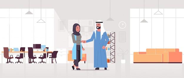 Ic ondernemers man vrouw handshaking arab zakenpartners paar handbewegingen tijdens vergadering overeenkomst partnerschap concept modern co-working centrum kantoor interieur volledige lengte horizontaal