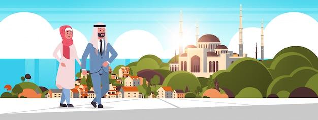 Ic paar wandelen buiten arabische man vrouw, gekleed in traditionele kleding arabische stripfiguren over nabawi moskee bouwen moslim stadsgezicht mooie kust achtergrond horizontaal