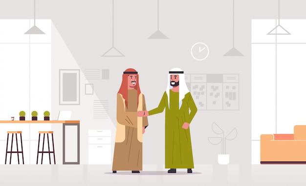 Ic zakenlieden handshaking arabische zakenpartners paar handbewegingen tijdens vergadering overeenkomst partnerschap concept modern co-working center kantoor interieur volledige lengte horizontaal