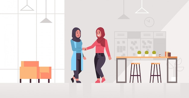 Ic zakenvrouwen handshaking arab zakelijke partners paar handbewegingen tijdens vergadering overeenkomst partnerschap concept modern co-working center kantoor interieur volledige lengte horizontaal