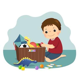 Illustratie cartoon van een kleine jongen zijn speelgoed in de doos. kinderen doen van huishoudelijke taken thuis concept.