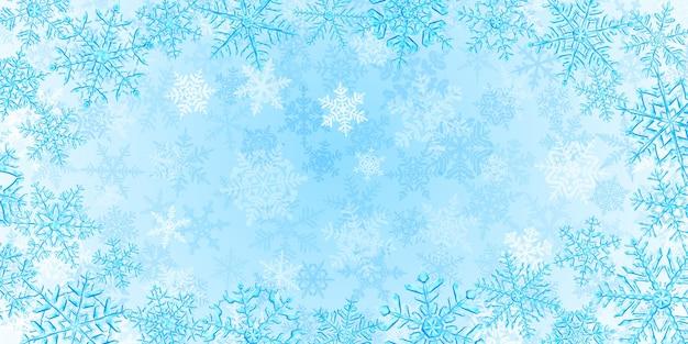 Illustratie van grote complexe doorschijnende kerstsneeuwvlokken in lichtblauwe kleuren, rondom gelegen op een achtergrond met vallende sneeuw
