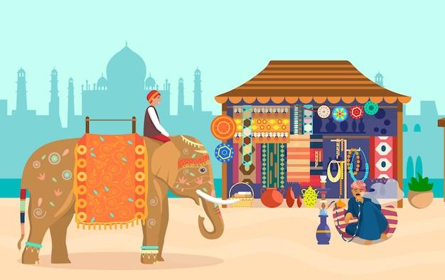 Indiaas landschap met olifantenruiter souvenirwinkel aardewerk tapijten stoffen