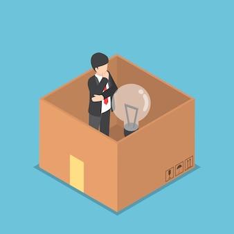 Isometrische zakenman met gloeilamp van idee in de papieren doos