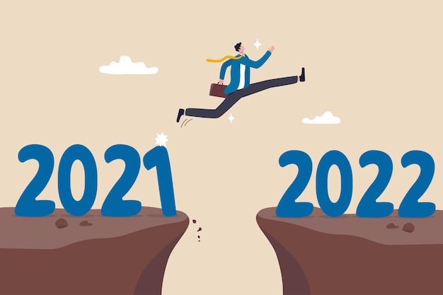 Jaar 2022 hoop, nieuwjaarsresolutie of succeskans, verandering naar nieuwe zakelijke mooie toekomst, overwin bedrijfsmoeilijkhedenconcept, ambitieuze zakenman sprong over jaarkloof van 2021 tot 2022.