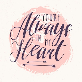 Je bent altijd in mijn hart-belettering of liefdesbelijdenis geschreven met kalligrafische lettertype tegen roze ronde verfvlek op achtergrond