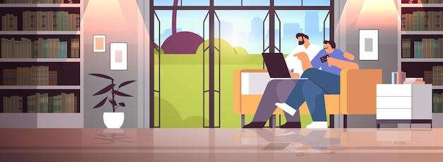 Jong koppel met creditcard met behulp van laptop online winkelconcept man vrouw samen goederen bestellen moderne woonkamer interieur horizontaal volledige lengte