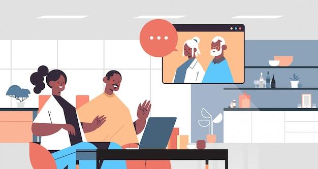 Jong koppel met virtuele ontmoeting met grootouders tijdens videogesprek familiechat online communicatieconcept keuken binnenlands portret horizontale illustratie