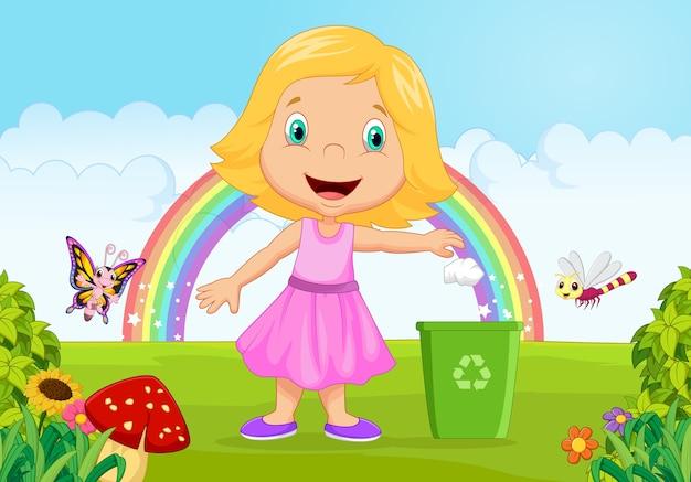 Jong meisje die afval gooien in draagstoelbak in de wildernis