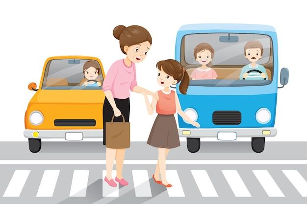 Jong meisje leidt oude vrouw de straat oversteken op zebrapad, auto's wachten hen