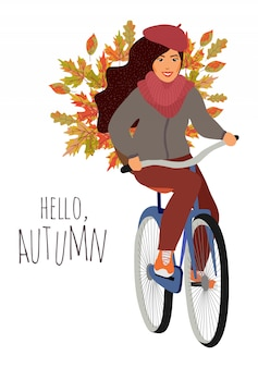 Jong meisje met een fiets met een mand van esdoorn en eikenbladeren.