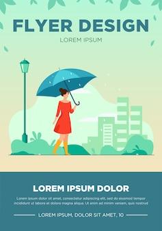 Jong meisje met oranje paraplu platte vectorillustratie. vrouw lopen bij regenachtig weer in park. stadsgebouwen flyer. regenseizoen.