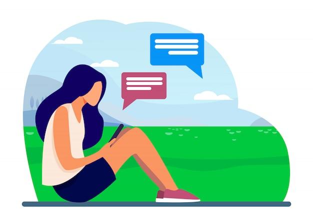 Jong meisje, zittend op het gazon met smartphone