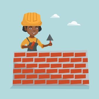 Jonge afrikaanse metselaar die een bakstenen muur bouwt.