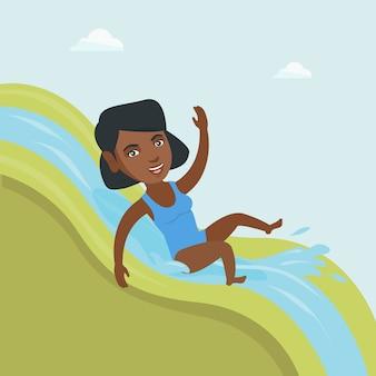 Jonge afrikaanse vrouw die onderaan een waterslide berijdt.