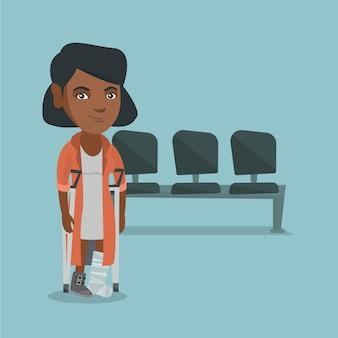 Jonge afrikaanse vrouw met gebroken been en krukken.