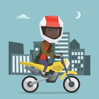 Jonge afrikaanse vrouw rijden op een motorfiets 's nachts.