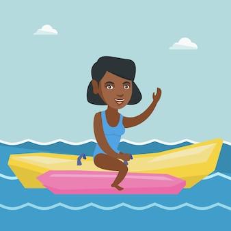 Jonge afro-amerikaanse vrouw die een banaanboot berijdt.