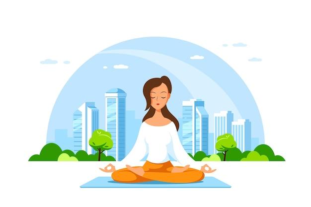 Jonge blanke vrouw zitten in lotus pose met grote stad. beoefening van yoga en meditatie, recreatie, gezonde levensstijl.