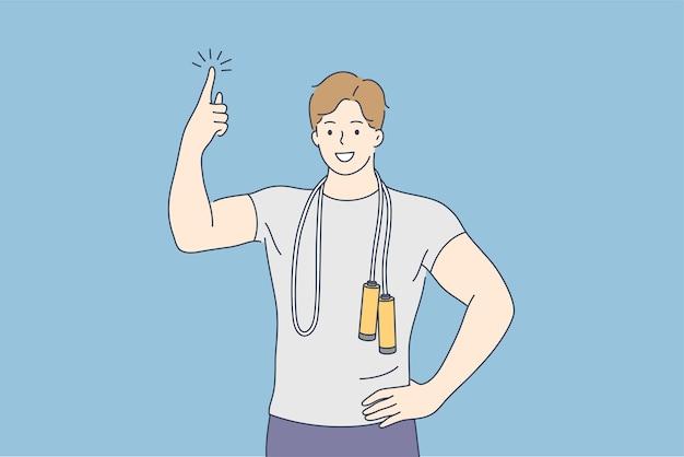 Jonge gelukkig lachende man jongen man atleet coach karakter staat met springtouw wijst vinger hierboven