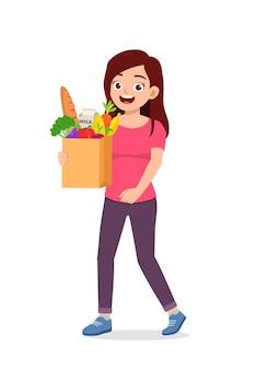 Jonge goed uitziende vrouw draagtas vol met kruidenierswaren