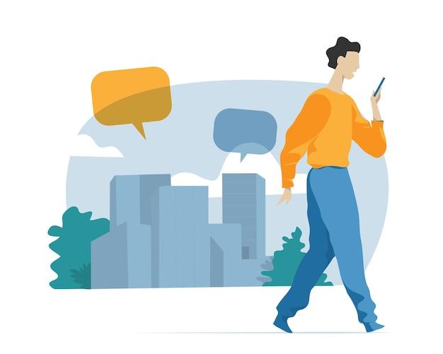 Jonge jongen die met mobiele telefoon op stedelijke achtergrond met toespraakbellen loopt