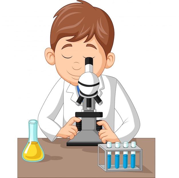 Jonge jongen die microscoop op het laboratorium gebruikt