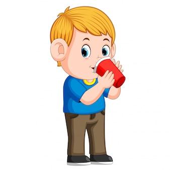 Jonge jongen drinken met een papieren beker