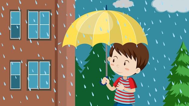Jonge jongen met paraplu die in regen loopt
