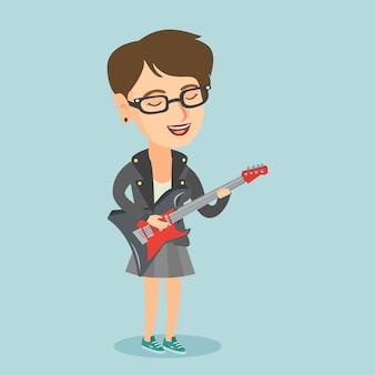 Jonge kaukasische vrouw die de elektrische gitaar speelt.