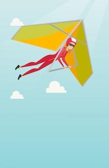 Jonge kaukasische vrouw die op deltavlieger vliegt