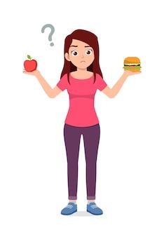 Jonge knappe vrouw kiest gezonde voeding of junkfood